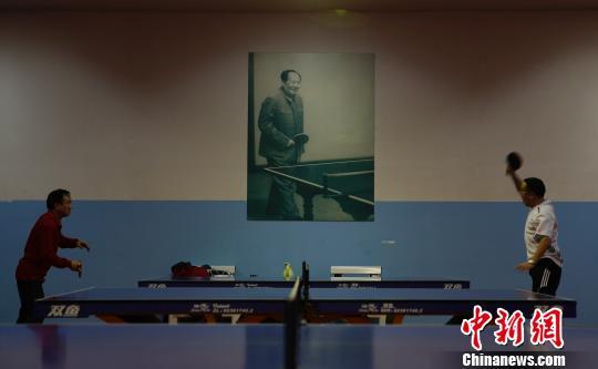 2013年春节长假期间,湖南一家体育馆内,民众打乒乓球健身,墙上挂着毛泽东打乒乓球的照片。近年来,越来越多的中国民众选择健身、旅游等健康的方式度过春节长假。中新社发 刘关关 摄
