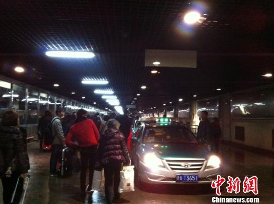 15日凌晨0时许,杭州城站火车站等待出租车的人群。 徐乐静 摄