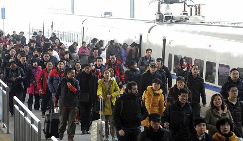 2月15日,抵达苏州火车站的旅客走向出站通道。新华社发(杭兴微 摄)