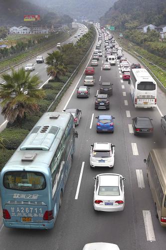 2月15日,排着长队的车辆缓慢有序地进入G15沈海高速浙江省温州市三都岭隧道。新华社发(庄颖昶 摄)