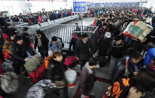 2月15日,在江西九江火车站候车室,大批旅客进站上车。新华社发(胡国林 摄)