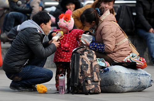 2月15日,一位小朋友和父母在郑州火车站东广场候车。新华社记者 李博 摄