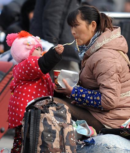 2月15日,在郑州火车站东广场,一位小朋友给妈妈喂方便面。新华社记者 李博 摄