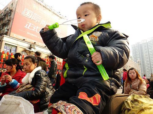 2月15日,一名小朋友在四川达州火车站外等待进站。新华社发(邓良奎 摄)