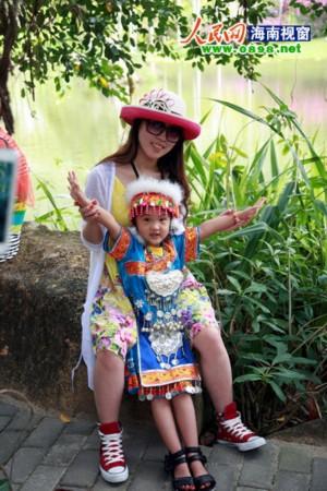 小朋友穿上少数民族服装与母亲合影