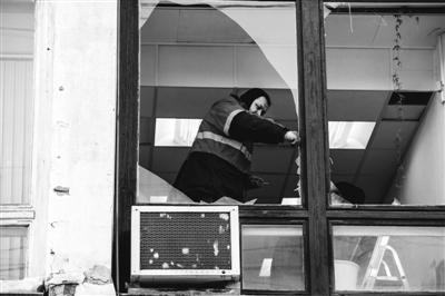 15日,车里雅宾斯克,陨石坠落造成大量玻璃被震碎,工人正在清理碎玻璃。