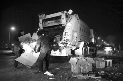 除夕夜,南四环西路,放完的烟花堆积路边,环卫集团的工人正将烟花皮装上环卫车。 新京报记者 尹亚飞 摄