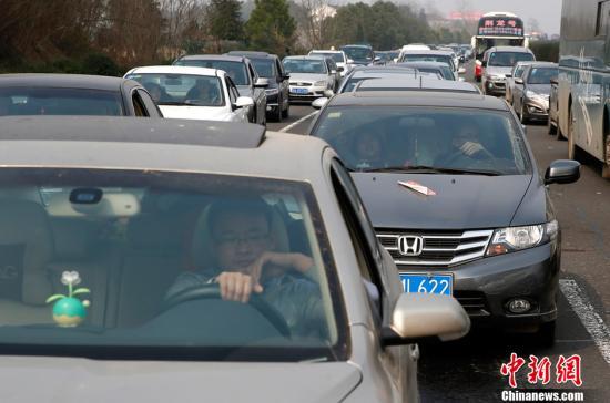 2月15日,京珠高速公路岳阳至长沙段的车辆明显增加,并不时发生拥堵现象。当日是2013年春节黄金周的最后一天,铁路、公路、民航都迎来节后返程客流高峰。为确保免费与收费工作的平稳过度,当日中午起各地高速公路陆续恢复发卡。中新社发 刘关关 摄