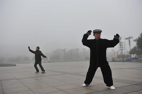 2月16日,浙江省临安市两名市民在浓雾中晨练。新华社发(胡剑欢 摄)