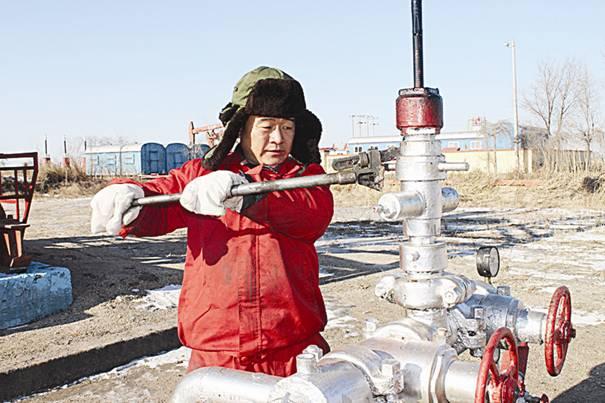 采油工严庭在用工具紧固井口盘根。