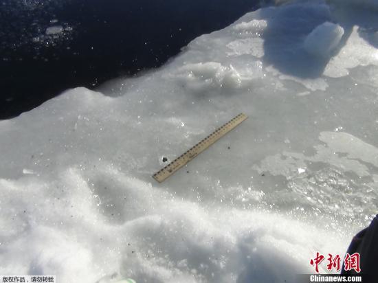 """当地时间2013年2月15日,俄罗斯车里雅宾斯克地区,陨石坠入冰冻的切巴尔库尔湖中形成的窟窿。该地区当天遭遇陨石雨""""袭击""""。"""