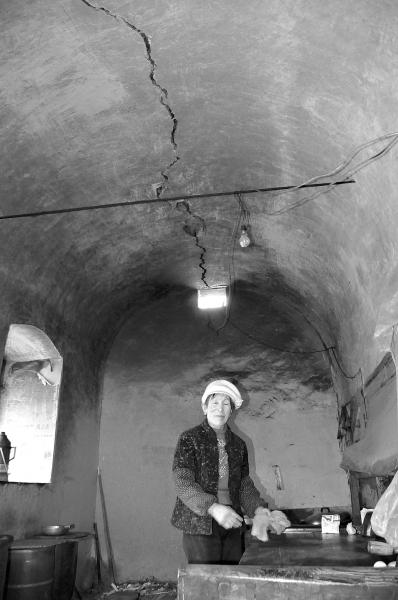 蛇年新春前夕,镇原县平泉镇麻王村村民张清芳在自家厨窑里收拾案板,她头顶窑背上一条长长的裂缝是石油勘探放炮时震出的。(本版照片均由记者王艳明摄)
