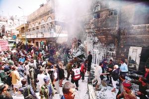 也门安全官员说,一架军用飞机当天在萨那市中心坠毁,造成至少9人死亡。图为2月19日,在也门首都萨那,消防员和军方人员试图扑灭飞机坠毁现场的火灾。