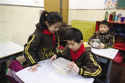 """昨日,体育馆路小学,""""饭长""""在检查组员是否剩饭。学校倡导节俭午餐,并设立""""饭长""""检查督促。新京报记者 侯少卿 摄"""