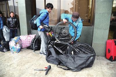 昨日,杭州火车南站,来自山东科技大学的李西亚和吴高伟将单车打包,准备坐火车返校。