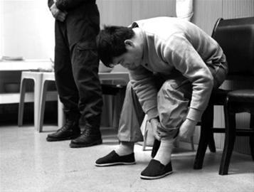 糯康被押赴刑场前的最后40分钟,在过渡监室中,糯康穿着灰色运动袜和黑色布鞋,他将袜子拉直,用裤子盖上 新华社发