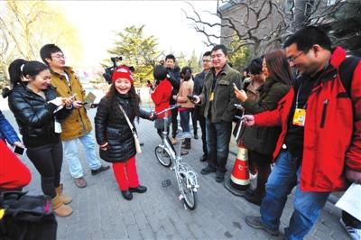 吴碧霞代表骑着自行车报到。本报记者张斌摄/视频