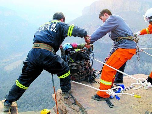 连着担架的安全绳被绑在崖顶的巨石上,为安全起见,救援人员又将自己与担架连在一起。