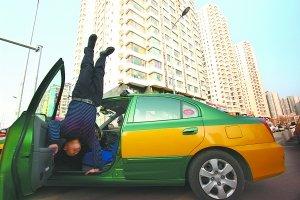 本报讯 路边趴活儿的时候,双手往车上一撑,在众人面前表演倒立。昨天下午在广安门外荣丰小区门前趴活的这位的哥,吸引了不少路人的目光。