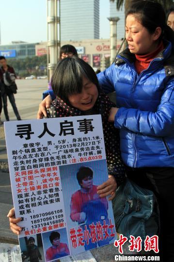 5岁男童章俊宇2月27日在南昌市中心八一广场失踪,其亲人连日来举牌寻人,感动无数网友。图为孩子的奶奶痛苦地拿着寻人启事,寻找自己的孙子。 姜涛 摄