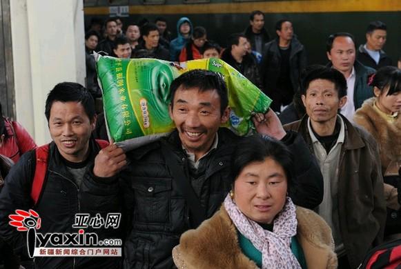 图为:2月4日17时18分,重庆开往乌鲁木齐<a href=http://search.huochepiao.com/huochezhan/>火车站</a>的L1133次类车抵达,42岁的王宝泉(中)走下火车,一想到今年有好几个工程要做,不由新上眉梢。亚心网记者 李铁军 摄