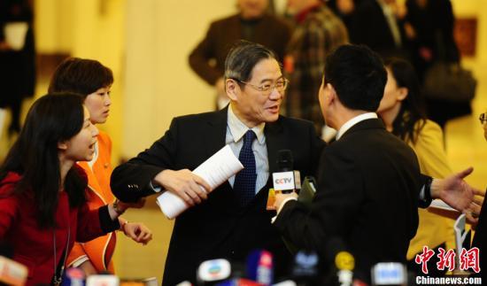 """3月5日上午,第十二届全国人民代表大会第一次会议在北京人民大会堂开幕。外交部副部长张志军(中)进入会场时,被记者""""拦截""""采访。中新社发 侯宇 摄"""
