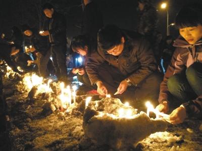 昨晚,长春市民主动到死者家门前的马路上,点起两排百米长的蜡烛。网友供图