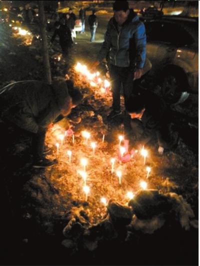 当地市民手捧蜡烛走上街头,送孩子最后一程。