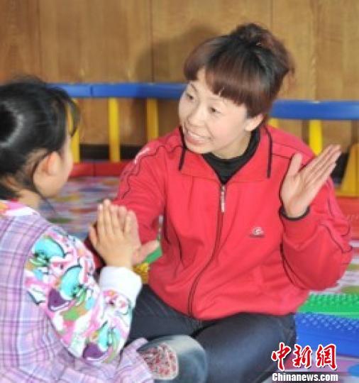 图为张素霞正在与患自闭症的孩子交流。 李永成 摄