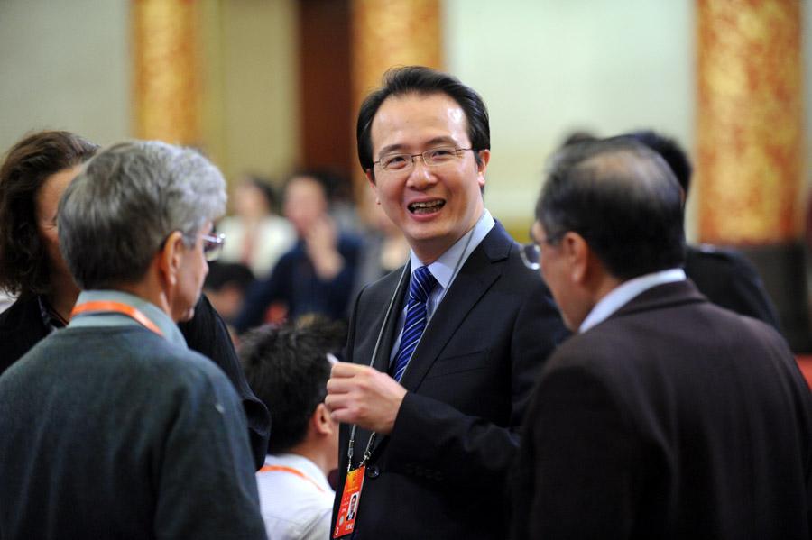 """3月9日,外交部发言人洪磊在记者会前与人交谈。当日,十二届全国人大一次会议举行记者会,外交部部长杨洁篪就""""中国的外交政策和对外关系""""答中外记者问。新华网/中国政府网 陈竞超"""