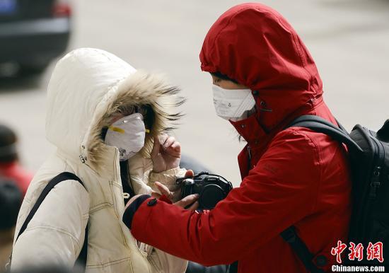 3月9日,北京市遭遇大风扬沙天气,阵风最大达8级。图为市民戴口罩出行。中新社发 刘震 摄