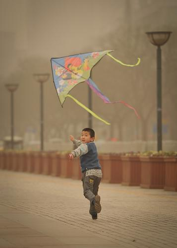 3月9日,在陕西省西安市新城广场,一名儿童在沙尘之中放风筝。新华社记者 丁海涛 摄