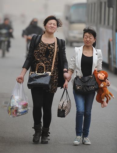 3月9日,在郑州街头,市民迎风出行。新华社记者 李博 摄
