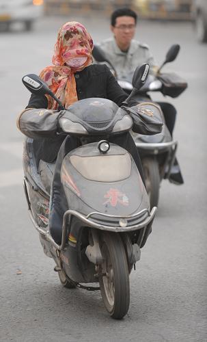 """3月9日,在郑州街头,一位市民""""全副武装""""骑行。新华社记者 李博 摄"""