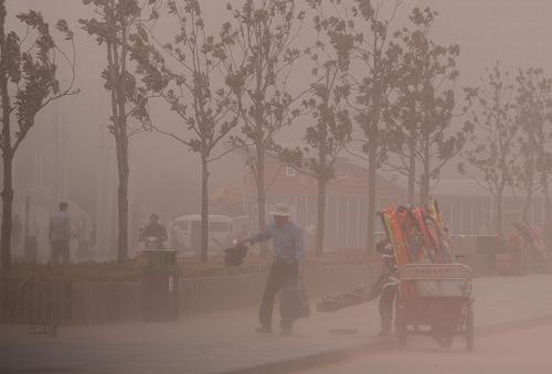 3月9日,在郑州郑东新区,一个卖风筝的摊主因风沙袭击而收摊离开。新华社记者 赵鹏 摄