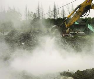 挖掘机在死猪处置点挖出深坑,工作人员身穿防护服再向深坑倾倒石灰。