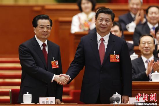 3月14日,十二届全国人大一次会议在北京人民大会堂举行第四次全体会议。习近平当选中华人民共和国主席和中华人民共和国中央军事委员会主席。图为习近平与胡锦涛握手。中新社发 盛佳鹏 摄