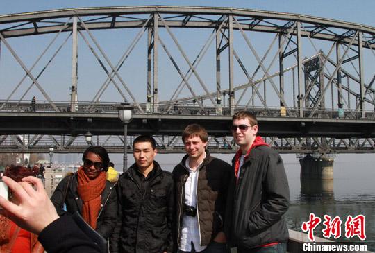 3月16日,中外国游客在辽宁省丹东市鸭绿江断桥景区合影。中新社发 司晓帅 摄
