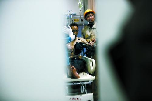 受伤农民工坐在病床上,在工友的帮助下,双手伸直,接受治疗