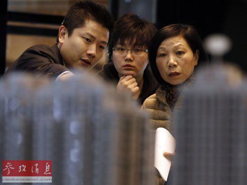 3月15日,购房者在上海之春房产展示交易会上查看楼盘模型。