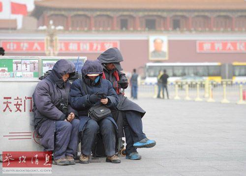 2月28日,在北京天安门广场上,几名摄影服务人员躲在摄影服务台后避风。新华社记者罗晓光摄