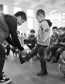 今天上午,沪上首次男幼师沙龙跨区研讨在浦东好儿童幼儿园举行,共同为男幼师寻找职业突破的良方,图为一名男幼师在公开课上教学生踢足球