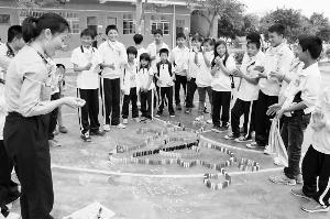 """志愿者与光明学校的孩子们用多米诺骨牌搭起""""会飞的梦想""""。"""