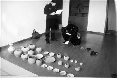 黄某将截留的部分盗墓品放置在展示柜上(警方身后)。警方供图
