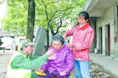 图为昨天下午,江先中夫妇在院子里给老母亲喂水、梳头。