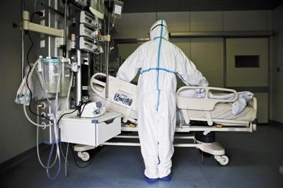3月19日,北皋附近的地坛医院ICU病房,一名身穿隔离服的护士正在整理病人的床铺。现在的隔离服轻薄透气,长期穿着要比过去的舒服很多。新京报记者 李飞 摄