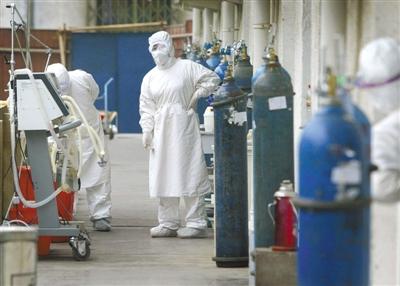 2003年4月17日,北京地坛医院,医生在SARS病房外检查氧气瓶。当时的隔离服又厚又不透气,长期穿隔离服工作,医护人员都觉得有缺氧的症状。