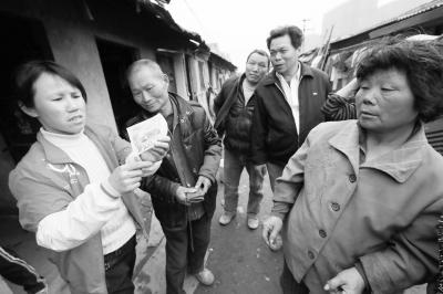 街坊邻居帮着贺爹爹查看假币,其中有几个人也曾经被骗子骗过。记者杨涛 摄
