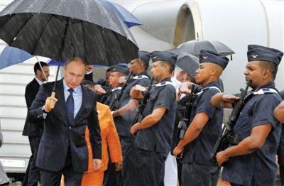 合作/26日,俄罗斯总统普京抵达德班国际机场,撑伞走下专机。