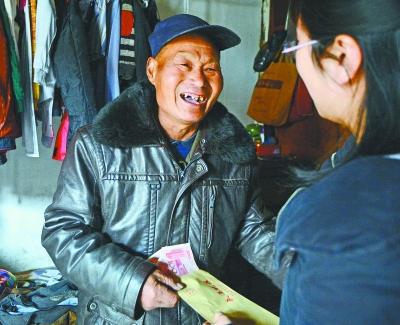 接过北京徐女士寄来的800元现金,贺爹爹露出感激的笑容。记者金思柳 摄